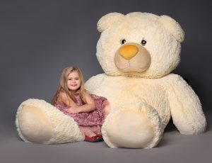 Baby sitting on the large teddy bear, stuffed animals, plush animals, big plush toys, kids and gifts, lilac dress, blonde girl, baby in studio,