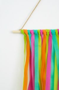Create your own colorful, on-trend wall hanging using strips of Oly*Fun. This simple project is quick and easy to make, and is a fun way to freshen up your decor for summer. It even becomes a unique way to display photos and mementos, making it a great DIY for dorm rooms!