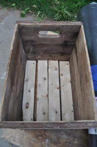 Antique crate reinforced to be more sturdy so it can function as an drink cooler